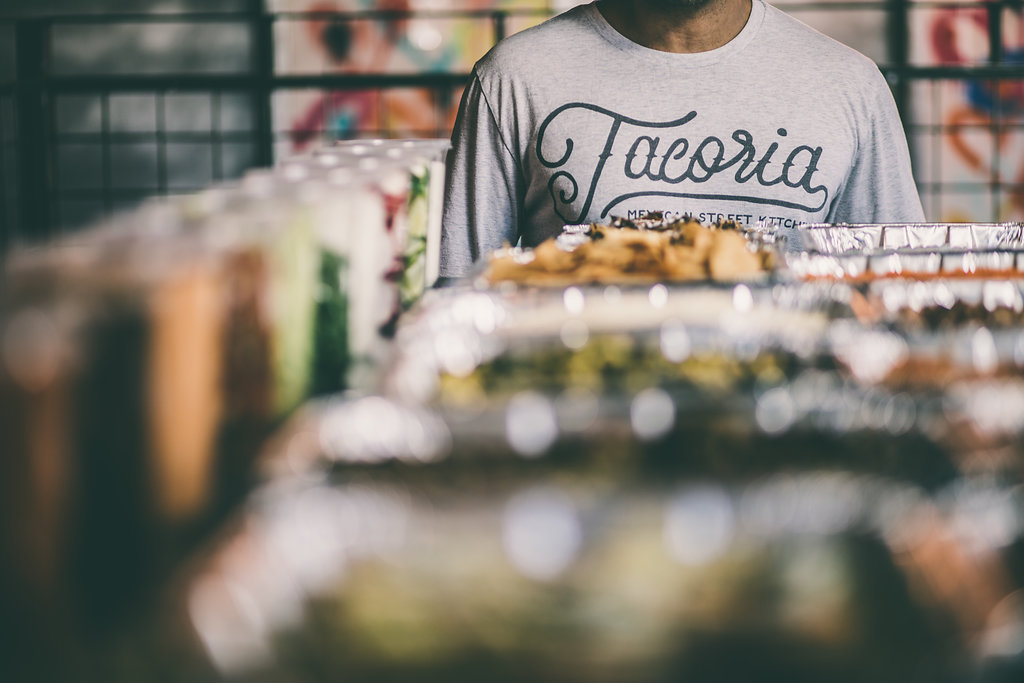 Person with Tacoria shirt next to catering trays of food